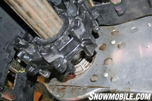 The driveshaft is inserted through the chain mounting bracket and into the chaincase.