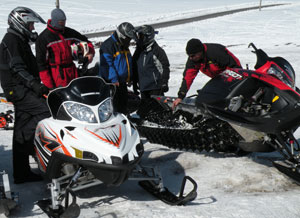 Snowmobile.com mountain rider Kevin Allred, at right, explains how the Polaris powder suspension works.